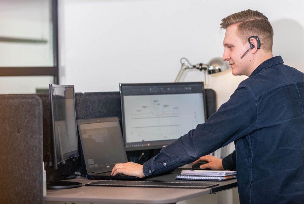 Kille som ritar på datorn med hjälp av CAD hur fibernätet ska ligga